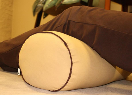 A bolster knee roll pillow is placed under your legs